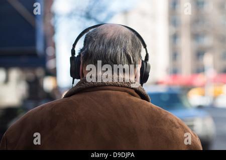 Rear view of senior man wearing headphones - Stock Photo