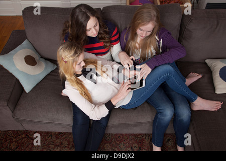 Girls sitting on sofa using digital tablet - Stock Photo
