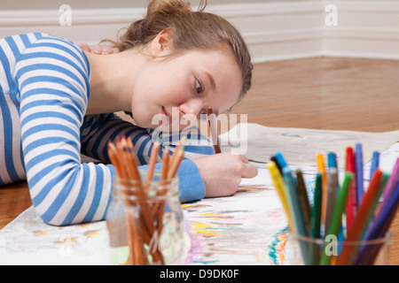 Girl lying on floor drawing picture - Stock Photo