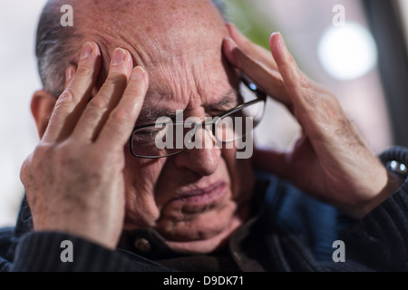 Senior man with eyes closed, wearing glasses, looking stressed - Stock Photo