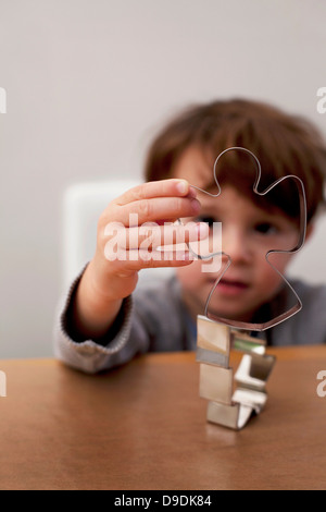 Boy looking through Christmas cookie cutters - Stock Photo