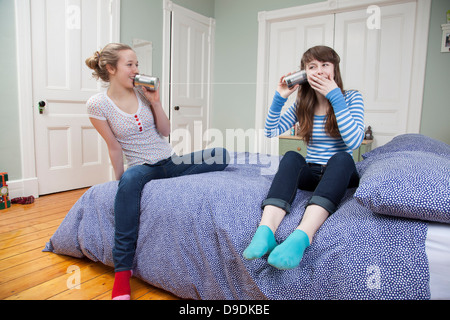 Girls sitting on bed playing with tincan telephone - Stock Photo