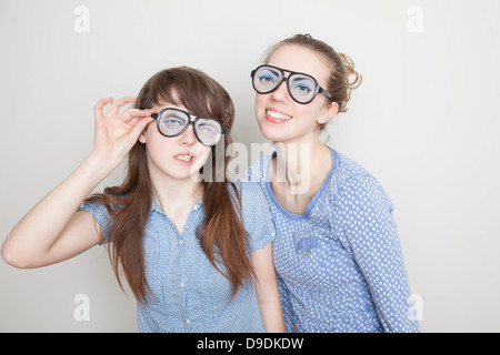 Two girls wearing fake glasses - Stock Photo