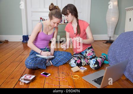 Girls sitting on bedroom floor with laptop, making friendship bracelets - Stock Photo