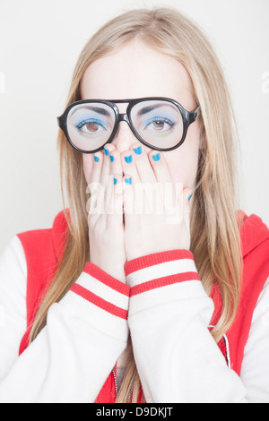 Girl wearing fake spectacles with hands covering her mouth - Stock Photo