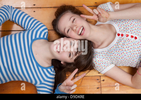 Girls lying on wooden floor doing peace signs - Stock Photo