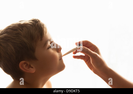 Cropped shot of mother's hand taking son's temperature - Stock Photo