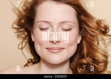 Studio shot of young woman with curly red hair, eyes closed - Stock Photo
