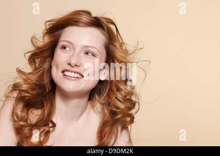 Studio shot of young woman with curly red hair - Stock Photo