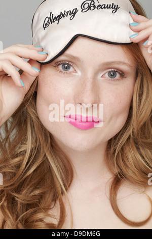Teenage girl wearing Sleeping Beauty eye mask on head - Stock Photo