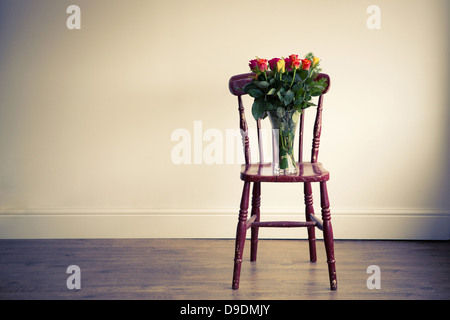 A Wooden Chair Holding A Vase Of Flowers In An Empty Room Stock