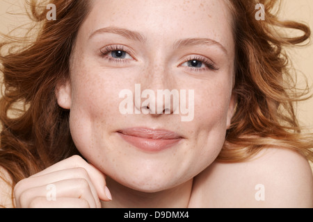 Studio shot of young woman with curly red hair, hand on chin - Stock Photo