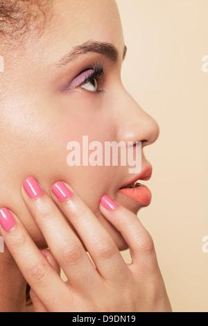 Side view of woman wearing make up and nail polish - Stock Photo