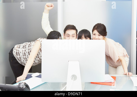 Colleagues looking at computer monitor, man punching the air - Stock Photo