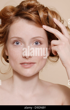 Young woman with curly red hair biting lip - Stock Photo