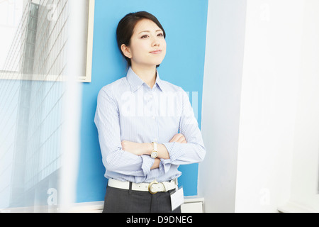 Portrait of woman with arms folded - Stock Photo