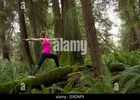 Mature woman performing warrior pose in forest - Stock Photo