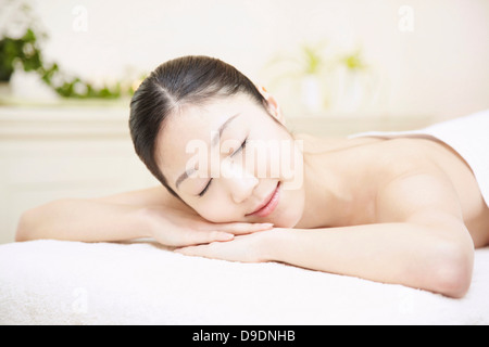 Woman lying on front in spa, eyes closed - Stock Photo