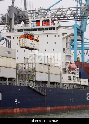 Containers being unloaded from a large carrier ship in the port of Rotterdam, the Netherlands - Stock Photo