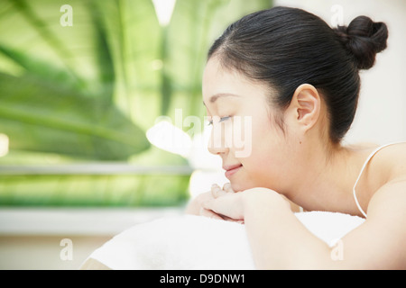Woman with hair bun lying on front - Stock Photo