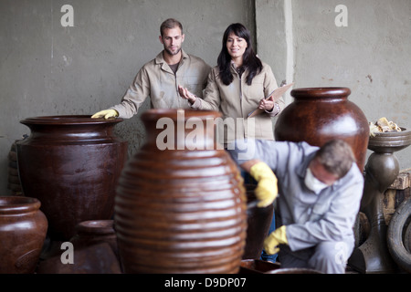 Painting and staining process in pottery factory - Stock Photo