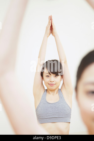 Woman with arms raised and hands together - Stock Photo