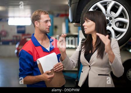 Car mechanic and customer discussing car repair - Stock Photo