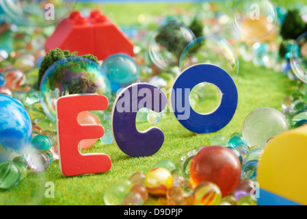 The word Eco on pretend grass with marbles - Stock Photo