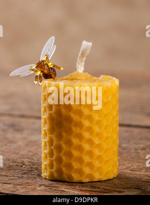 Beeswax candles on wooden table - Stock Photo