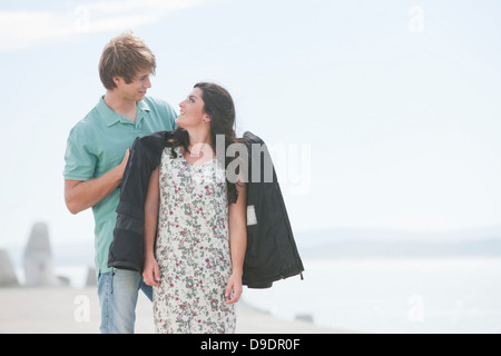Romantic young couple standing on pier - Stock Photo