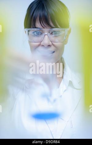 Woman holding up laboratory beaker - Stock Photo