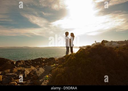 Young couple hugging on coastline - Stock Photo