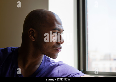 Close up portrait of mid adult male looking out of window - Stock Photo