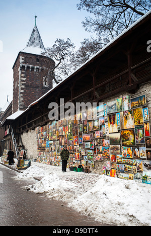 Selling posters along Painters Wall behind Krakow Barbican, historic gateway leading into the Old Town of Krakow, - Stock Photo