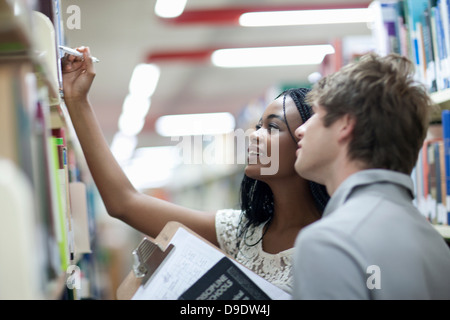 Students choosing books in library - Stock Photo