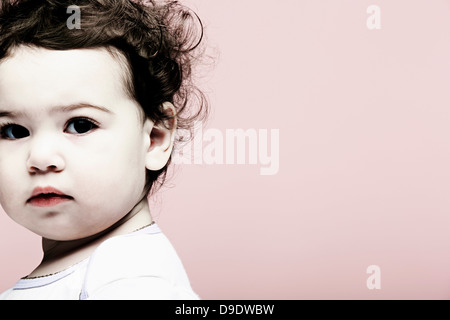 Portrait of baby girl against pink background - Stock Photo