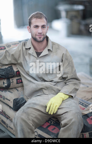 Man sitting on stack of cement bags - Stock Photo