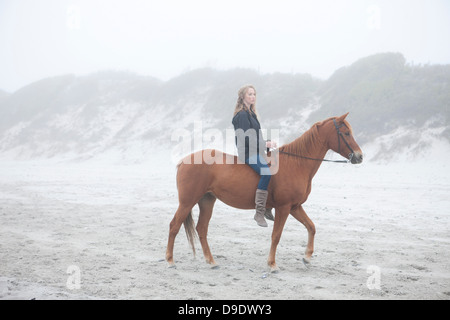 Woman riding horse on beach - Stock Photo