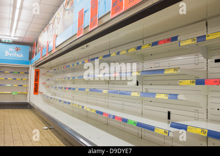 no food on rows of empty shelves at a branch of Lidls discount supermarket UK - Stock Photo