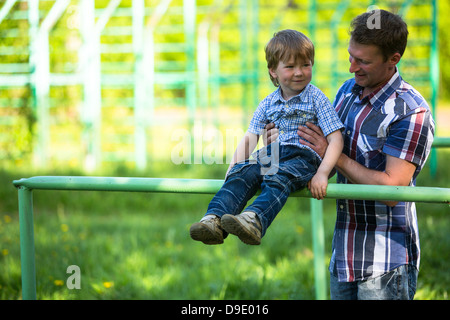 Father and son playing on the playground - Stock Photo