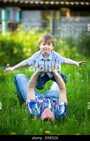 Father and son playing in the park lying on the grass - Stock Photo