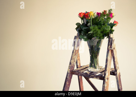 A Wooden Stepladder Holding A Vase Of Flowers Placed In An Empty