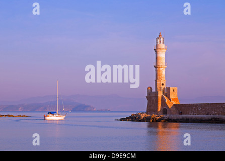 Chania's centuries old lighthouse in Venetian Harbour and boat in early morning - Stock Photo