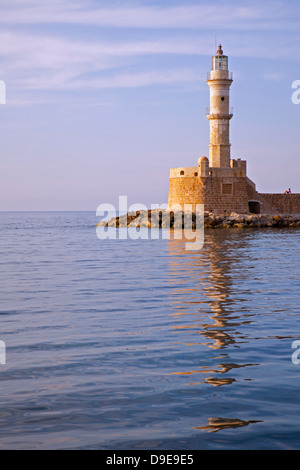 Person sitting beside Chania's centuries old lighthouse in Venetian Harbour - Stock Photo
