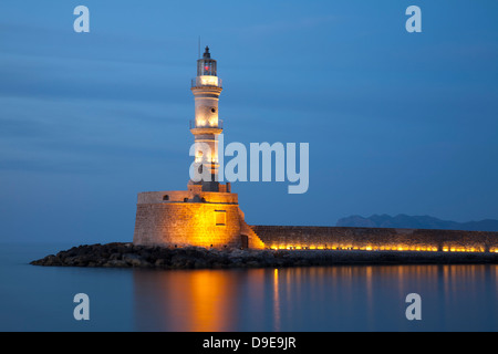 Chania's centuries-old lighthouse in Venetian Harbour at night - Stock Photo