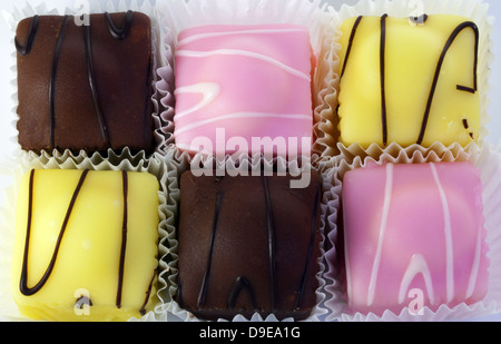 Fondant fancies - small individual iced sponge cakes close-up. - Stock Photo