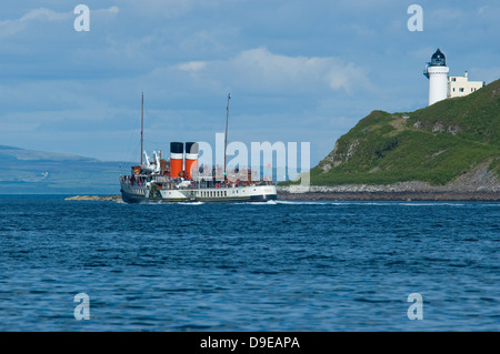 The Waverley the last sea going paddle steamer in the world on a pleasure excursion from Campbeltown passing a lighthouse. - Stock Photo
