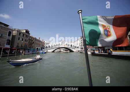 BOAT RIALTO BRIDGE & FLAG VENICE ITALY 13 July 2012 - Stock Photo