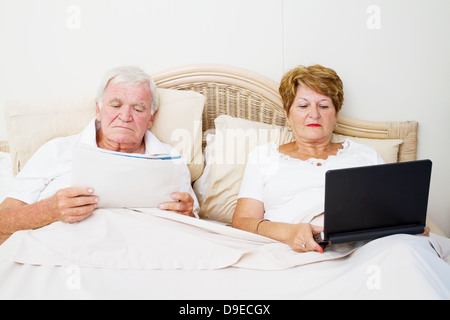 senior couple reading in bed before sleep - Stock Photo