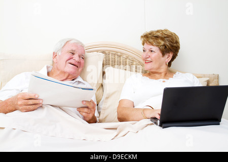 senior couple chatting in bed before sleep - Stock Photo